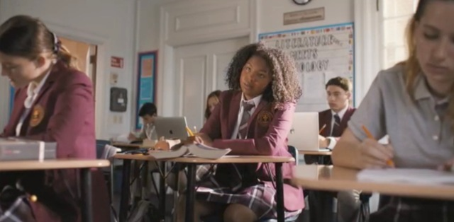 Angelica sits at her desk in her school uniform, bored