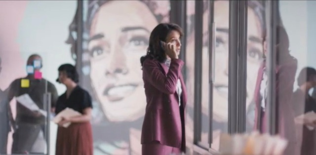Bette Porter, in a mauve pantsuit is on the phone in her office standing in front of a large painting of Bette