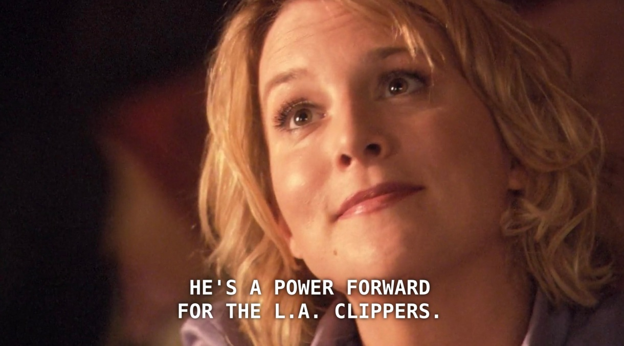 """Tina, wearing a purple blouse and her hair in curls, looks up at a new client, who has just asked her what her husband does for work. Tina says, """"He's a power forward for the L.A. Clippers."""""""