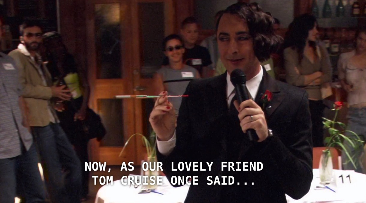 """Billie is wearing a black suit, white shirt, black tie, and a monocle, and is holding a microphone in one hand and a long cigarette in the other. He is hosting Bisexual Speed Dating in a crowded room of people. He announces to the crowd, """"Now, as our lovely friend Tom Cruise once said, the bar is open!"""""""