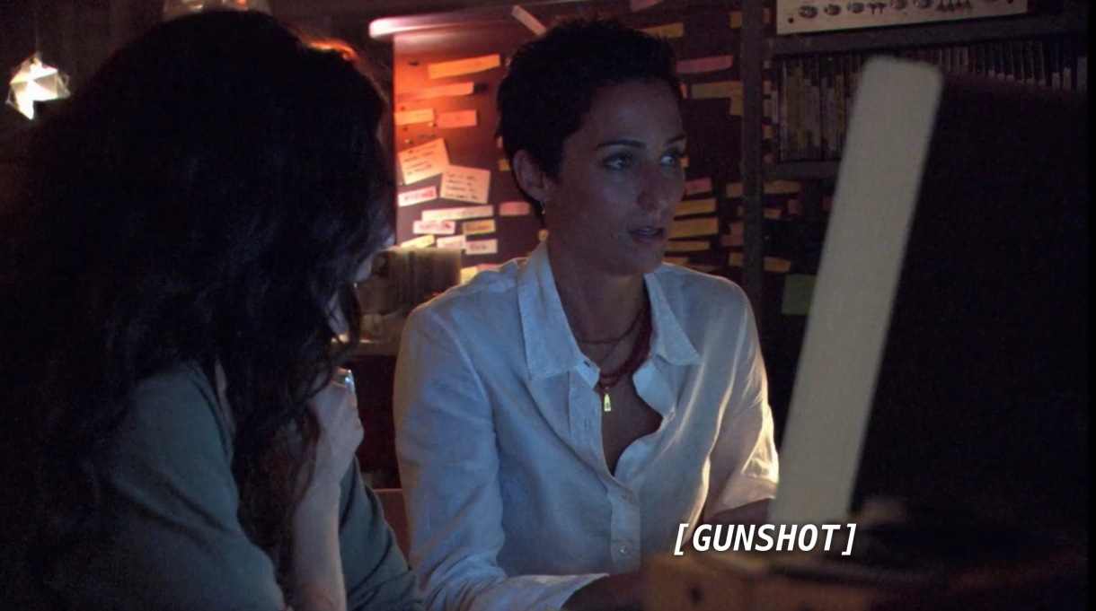 Helena and Dylan sit in front of a computer screen in a dark room. The sound of a gunshot comes from the computer.
