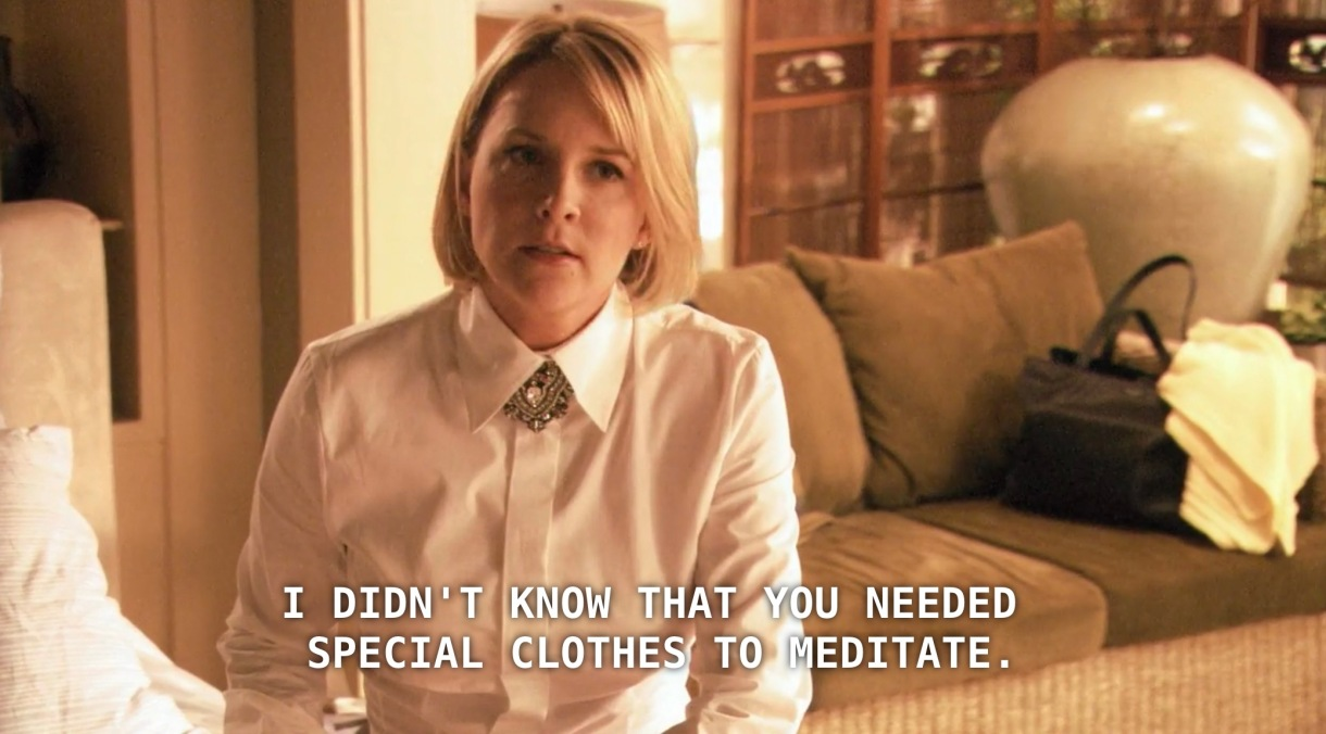 """Tina (with straight blonde hair and a white shirt buttoned up all the way) sits in her house. She says to Bette, """"I didn't know that you needed special clothes to meditate."""""""