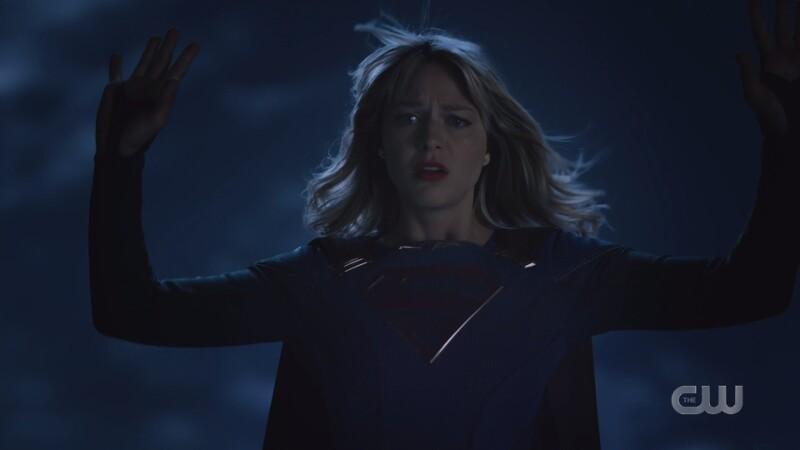Supergirl holds up her hands in surrender