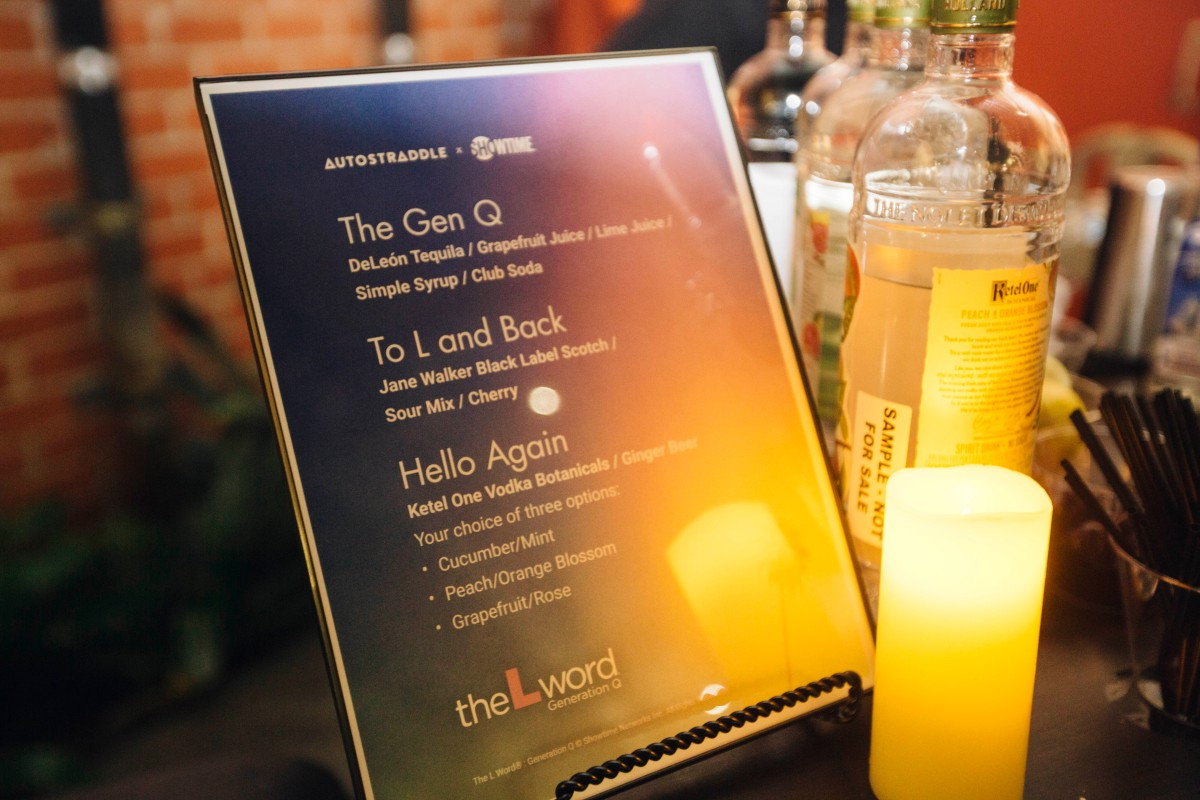 A photo of the drink menu with L Word-themed drinks, propped up next to a lit candle and bottles of liquor.