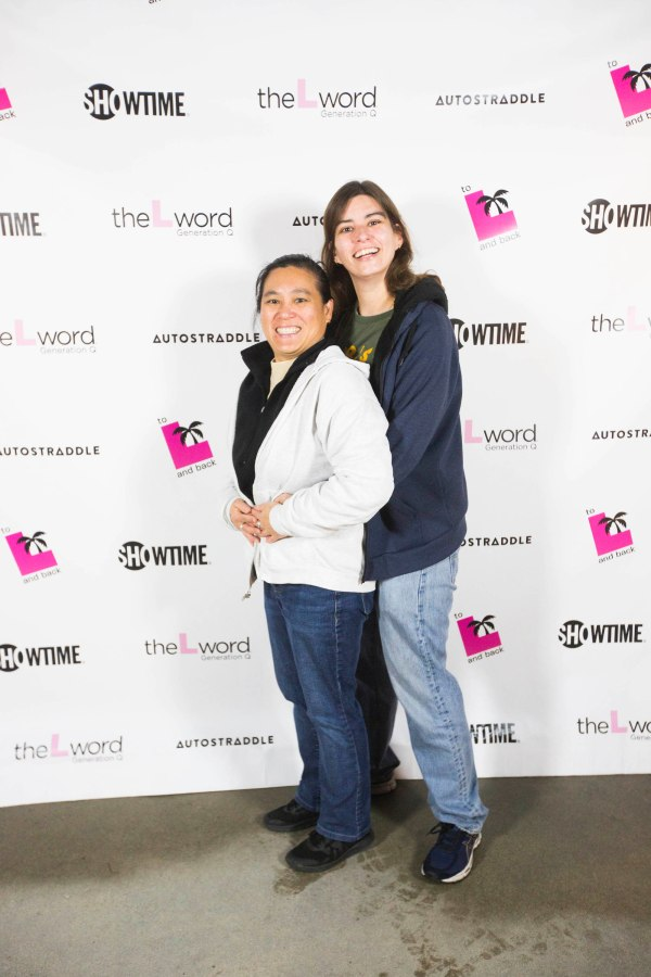 """Two people posing """"prom style"""" in front of a promo poster for """"The L Word: Generation Q."""" The person standing behind is wearing jeans and a blue hoodie. That person has their arms around a person standing in front of them, who is wearing blue jeans and a white jacket."""