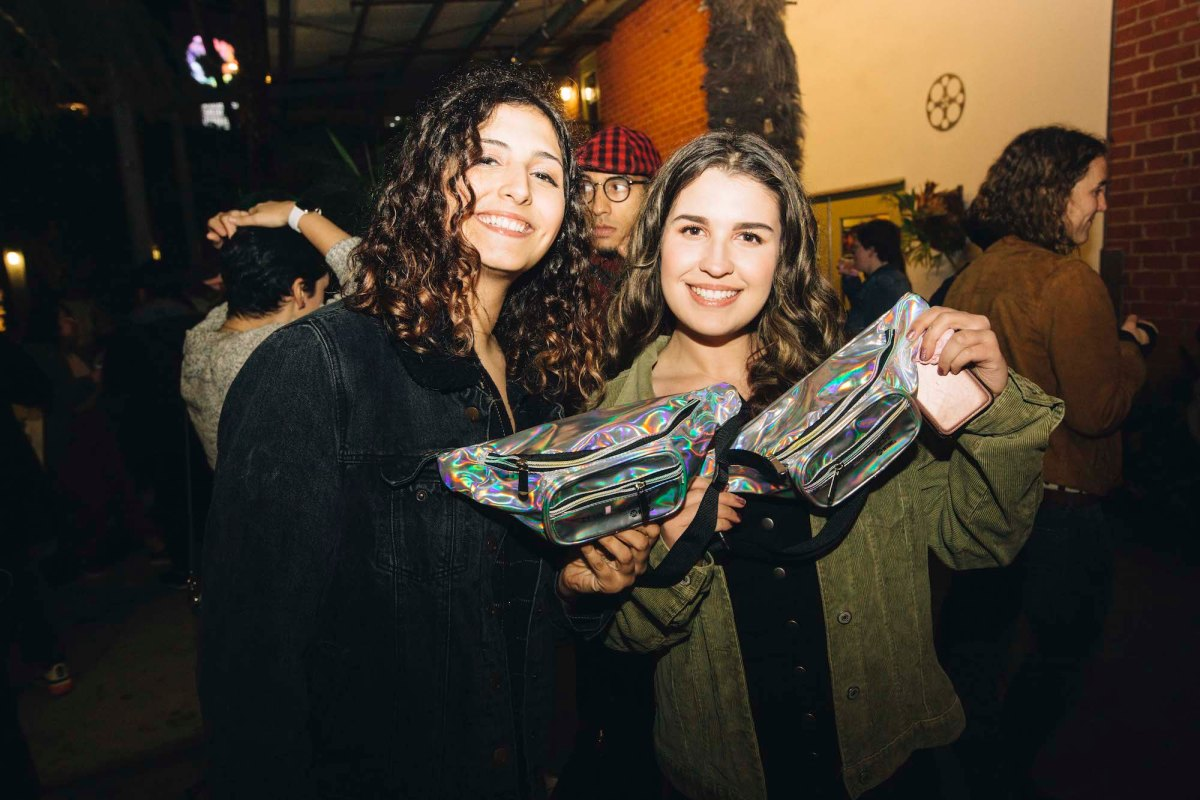 Two people posing with their silver sparkly fanny packs from the merch table. They are both smiling.