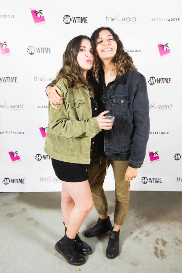"""Two people with their arms around each other in front of a promo poster for """"The L Word: Generation Q."""" The person on the left is wearing a black mini skirt and green jacket. The person on the right has tan pants and a black denim jacket."""