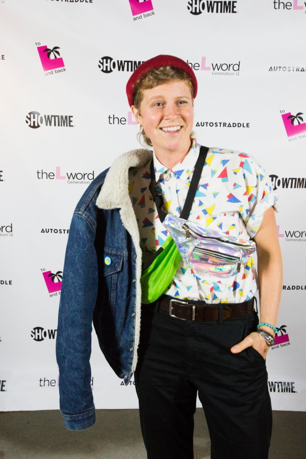 """A person posing in front of a promo poster for """"The L Word: Generation Q."""" They are wearing a brightly colored patterned button-up, two fanny packs crossing their chest, and a denim jacket draped over their right shoulder."""