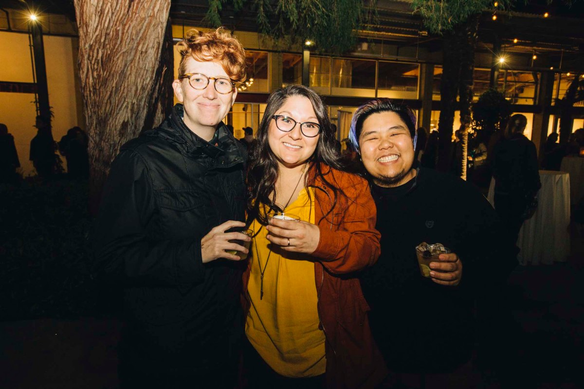 Three people posing for a photo. The one on the left has short red hair, glasses, and a black shirt. The one in the middle is wearing a yellow shirt and a red jacket, glasses, and long brown hair. The one on the right is wearing a black shirt, has short dark hair, and facial hair.