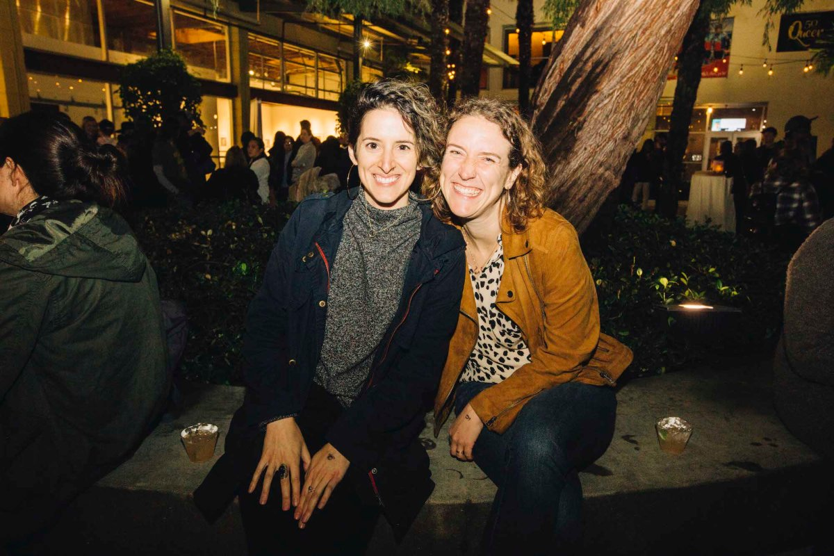 Two people sit outside on a bench and pose for a photo, smiling.