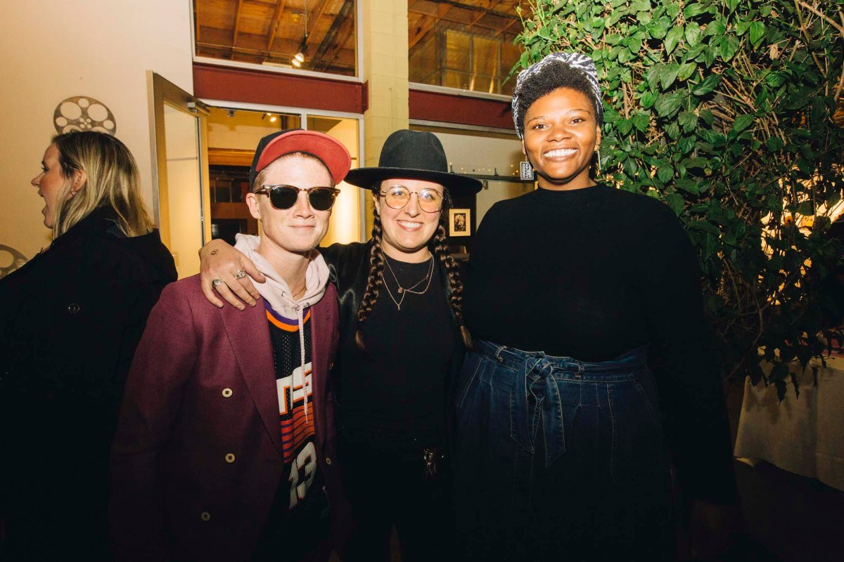 Three people stand next to each other, posing for a photo. The one on the left is wearing a maroon jacket, sunglasses, and a baseball hat. The person in the middle is wearing all black, two braids in their brown hair, and glasses. The person on the right is wearing a high-waisted denim skirt, a black top, and a headscarf.