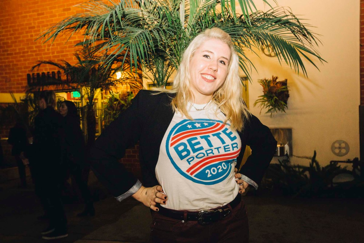"""A blonde-haired person wearing a """"Bette Porter 2020"""" t-shirt under a black blazer. They are smiling in front of a palm tree."""