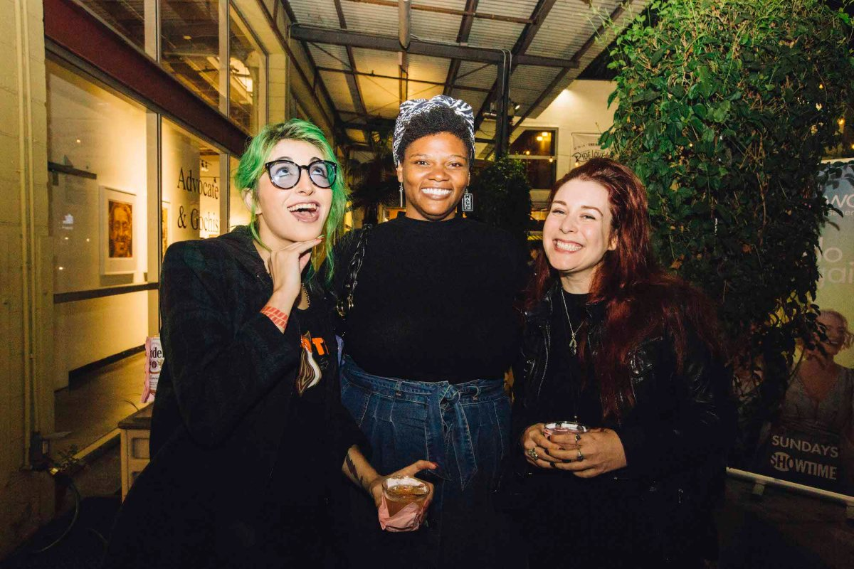 Three people posing for a photo. The one on the left has green hair and is wearing all black and glasses. The person in the middle is wearing a denim skirt, black top, and a headscarf. The person on the right has long dark red hair and is wearing all black.