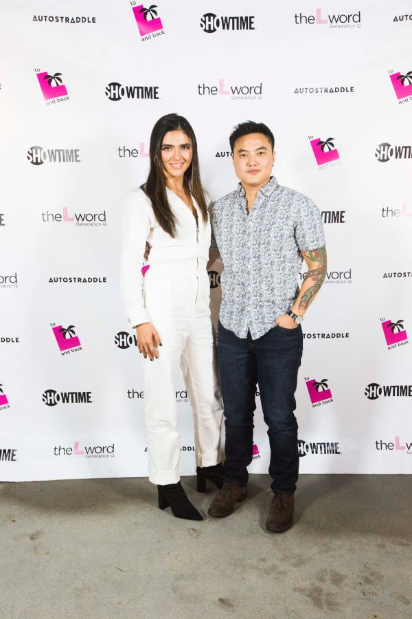 """Arienne Mandi (in a white jumpsuit and black ankle boots) and Leo Sheng (in dark jeans and a black-and-white patterned button-up shirt) posing in front of a promo poster for """"The L Word: Generation Q."""""""