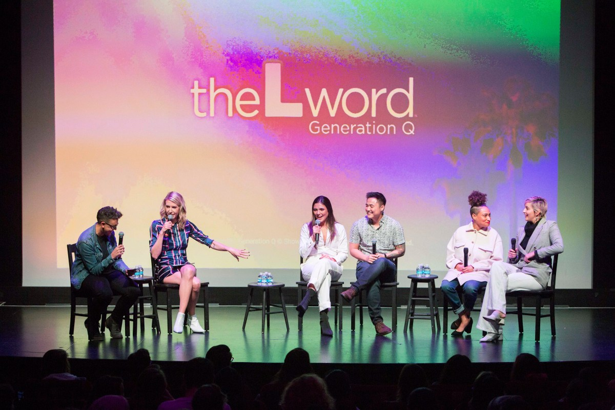"""Carly and Riese on stage next to Arienne Mandi (Dani), Leo Sheng (Micah), Rosanny Zayas (Sophie) and Jacqueline Toboni (Finley). The screen in the background has the logo for """"The L Word: Generation Q"""" projected onto it."""