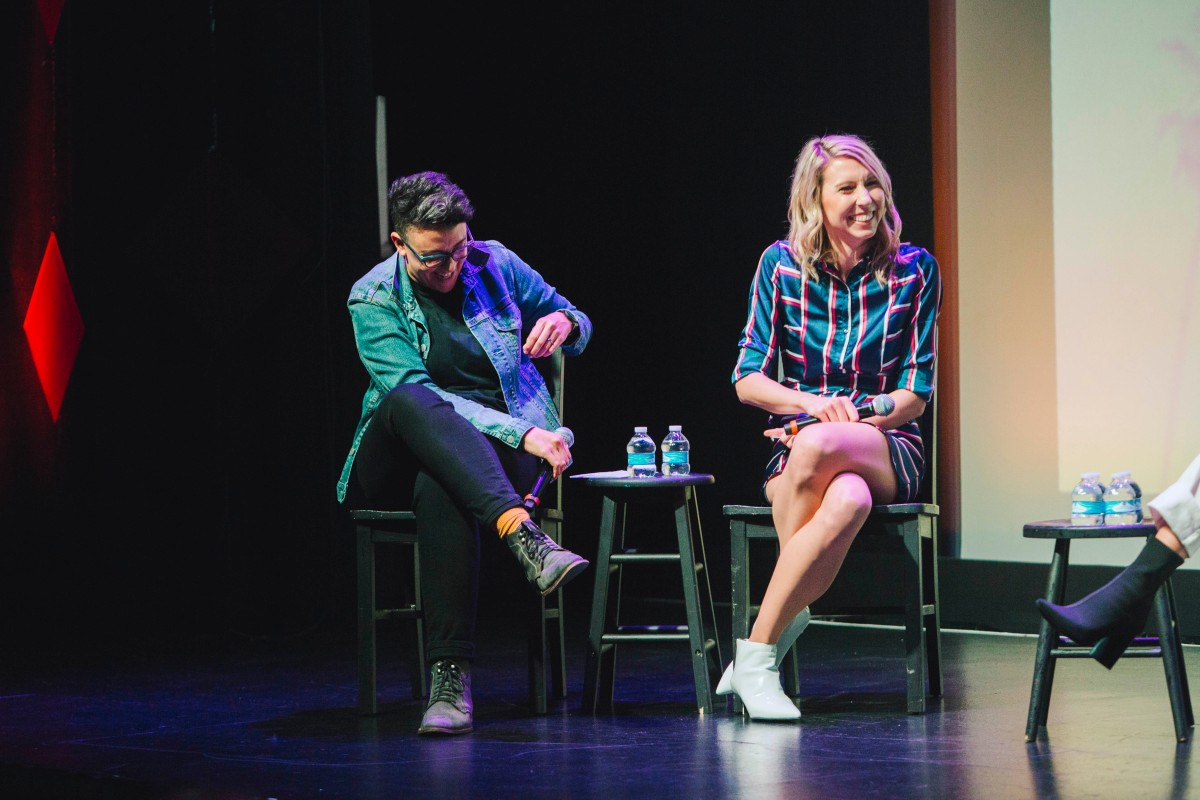 """The """"To L and Back"""" hosts Carly Usdin and Riese Bernard sit next to each other on stage. Carly is wearing black jeans and a chambray shirt, and Riese is wearing a blue, red, and white striped dress."""