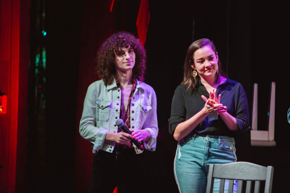 Drew Gregory and Analyssa Lopez stand on stage.