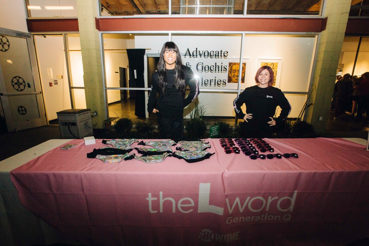 """Two people standing behind a merch table with a pink tablecloth with the logo for """"The L Word: Generation Q"""" printed on it. The person on the left is wearing all black, and has long dark hair and bangs. The person on the right is also wearing all black and has short auburn hair. Both are looking at the camera and smiling."""