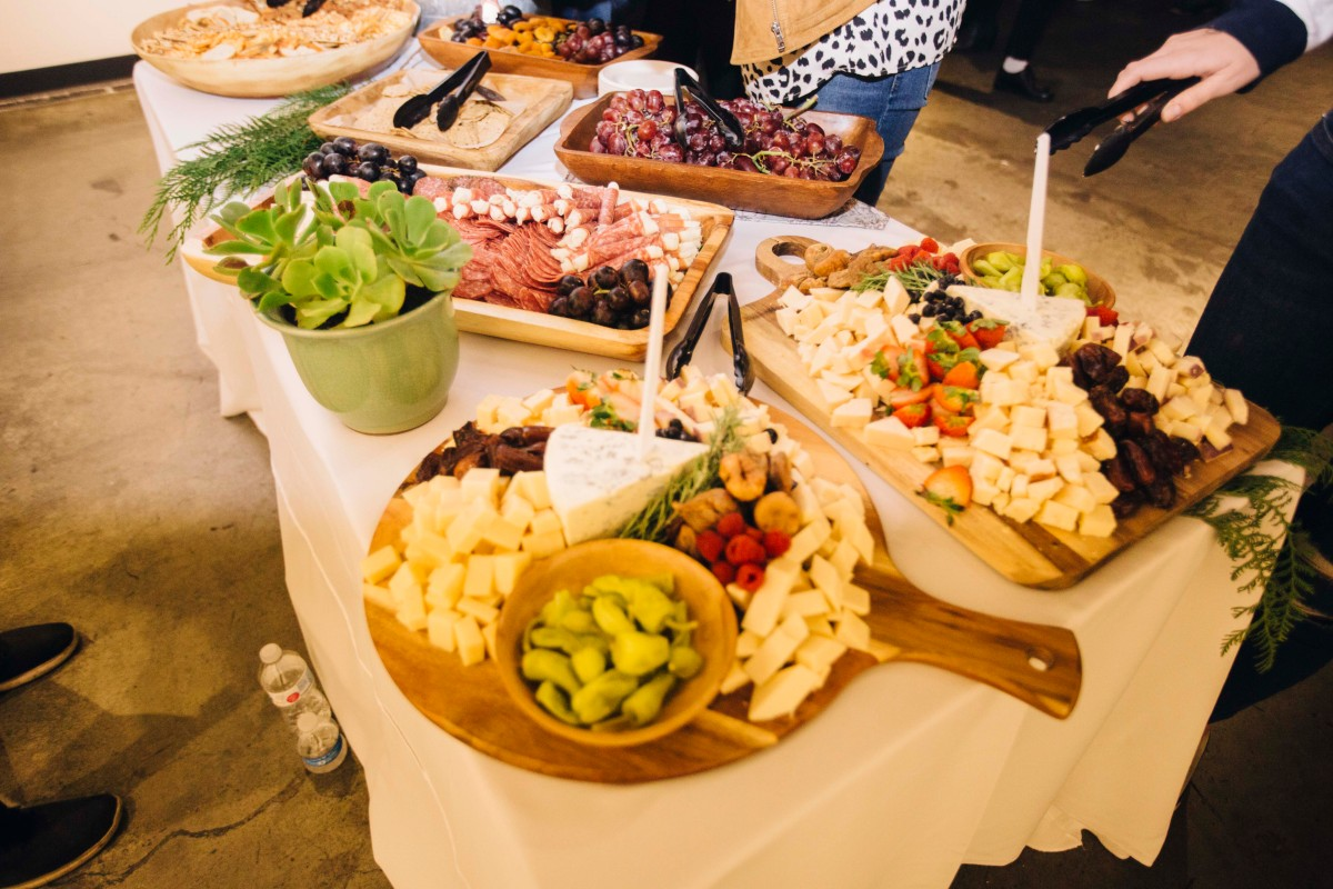 A photo of the food table, featuring multiple different meat and cheese plates.