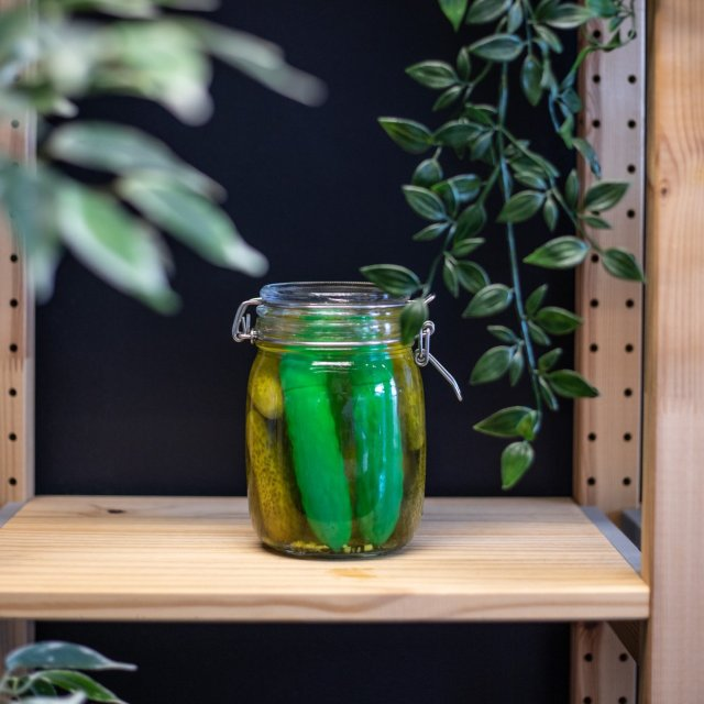 a pickle-shaped vibrator in a jar of actual pickles on.a shelf