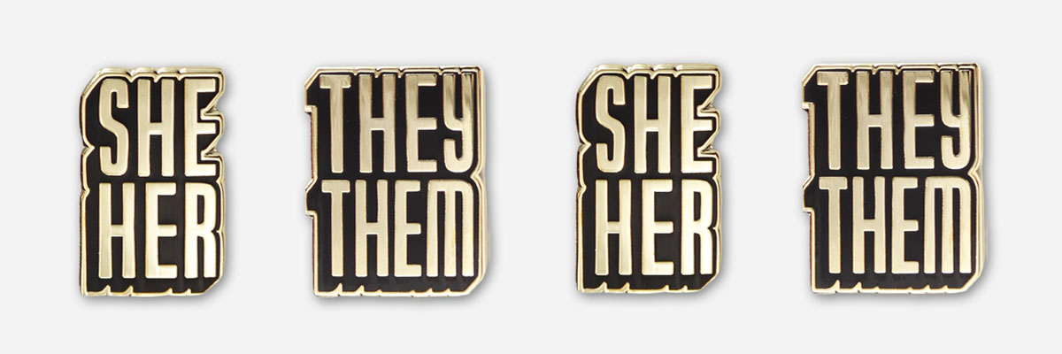 autostraddle merch she/her and they/them pronoun pins