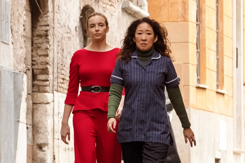 Image: Jodie Comer as Villanelle in a sharp red dress, Sandra Oh as Eve Polastri wearing a blue pajama-type top over a green turtleneck? It sounds weird but it is weird. they're walking down a european street of some kind, it seems like villanelle is following eve