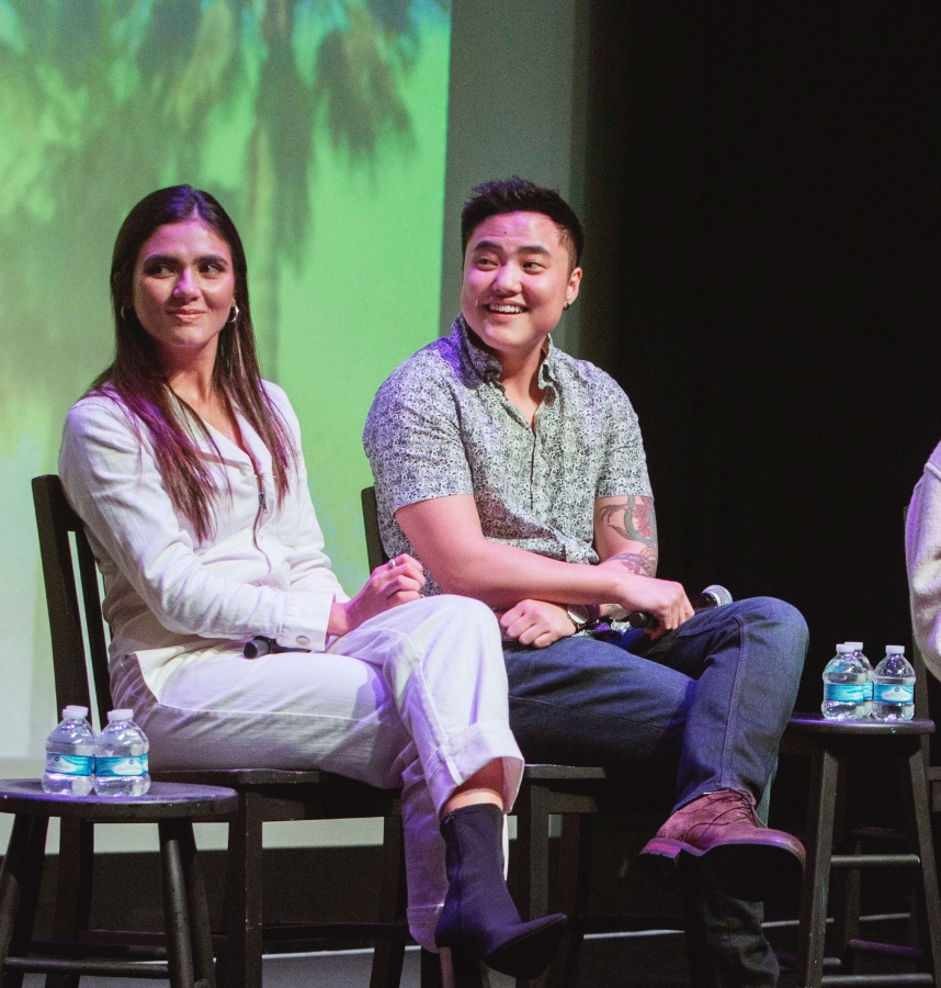 Arienne Mandi and Leo Sheng sit next to each other on stage. They are both smiling and looking to their right.