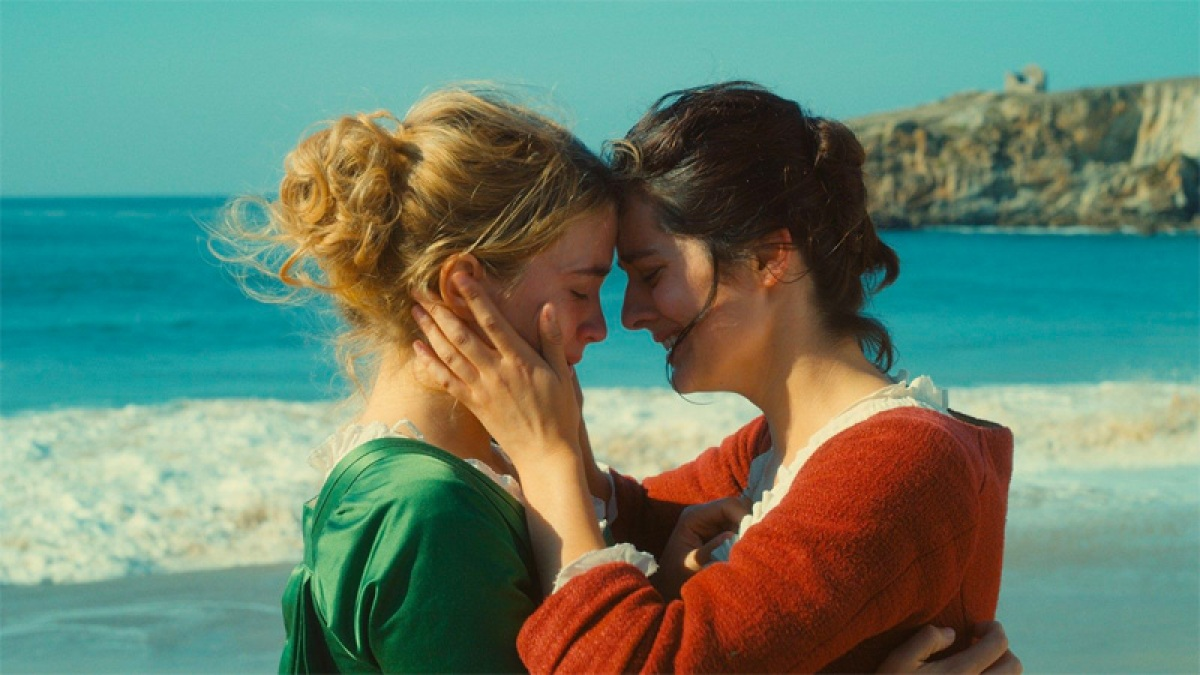 "A screenshot of ""Portrait of a Lady on Fire"" in which one woman holds another woman's face on a beach. This is a lesbian movie available for streaming on Hulu."
