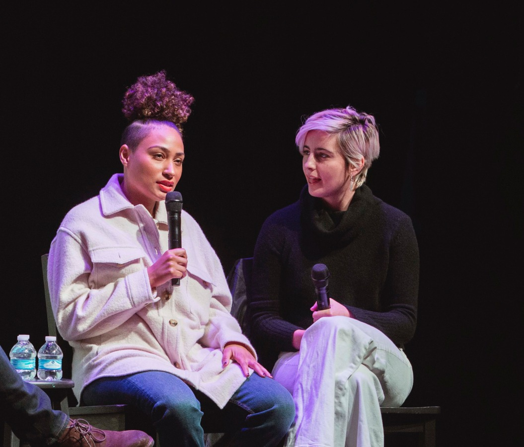 Rosanny Zayas and Jacqueline Toboni sit next to each other on stage. Rosanny is speaking into the microphone and Jacqueline is looking at her and listening intently.