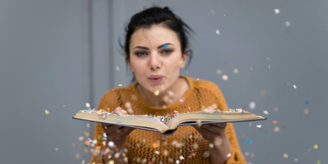 woman in a mustard sweater blowing confetti off an open book at the camera