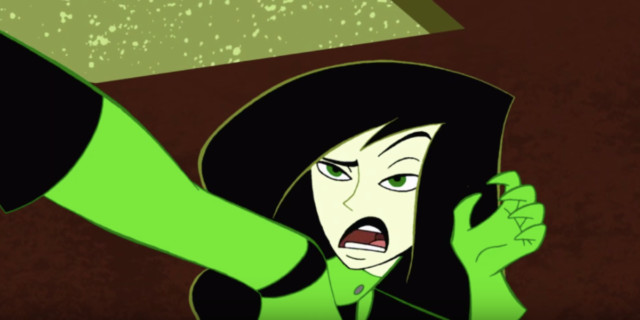 Shego, a young woman from Kim Possible, has Black hair, pale skin, and green eyes. She is pinning someone to a wall with one hand, and holding her other hand up toward her face.