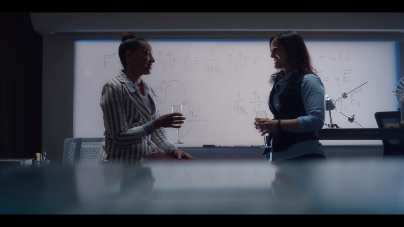 Samantha Burns and Amanda wear business outfits in a lab