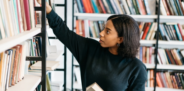 woman in a library holding a book and reaching for another on a shelf