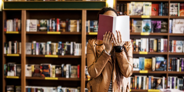 person in a tan jacket in a bookstore holding a book open over their face