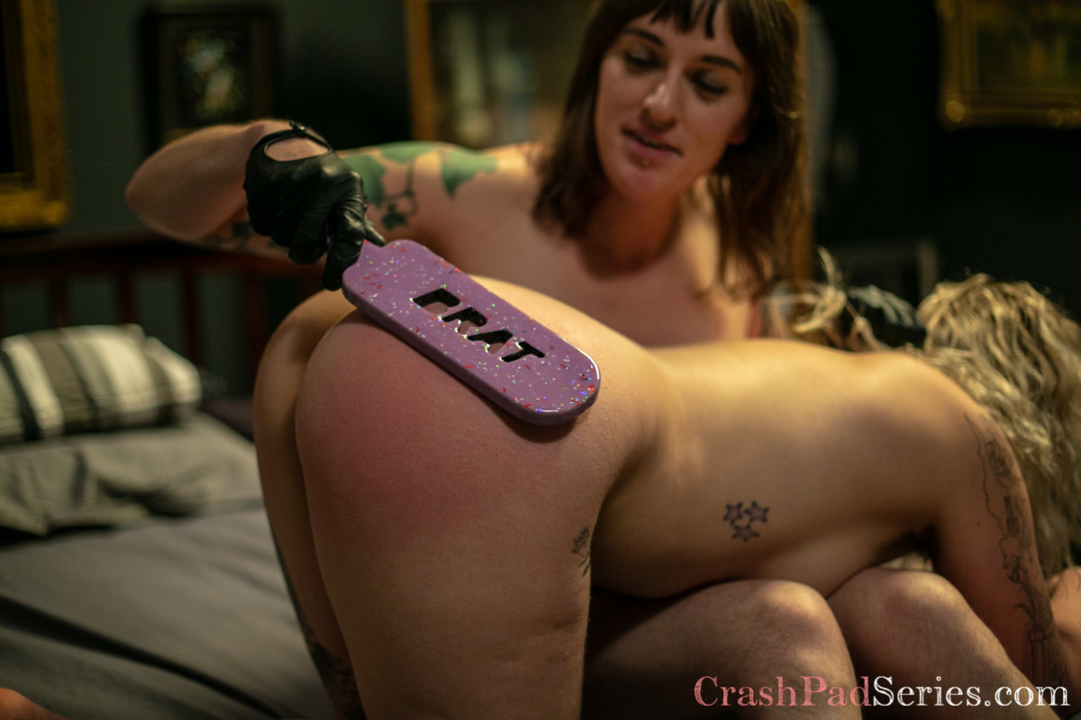 """Emma Claire and Lilian Rose doing a spanking scene with a paddle that reads """"brat"""""""