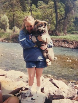 12 year-old Queer Girl holding an enormous fluffy gray puppy