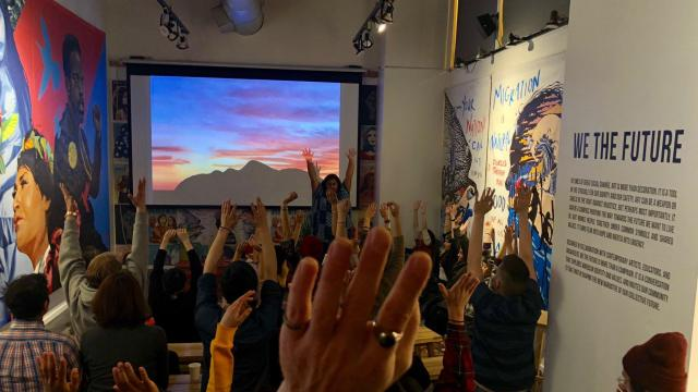 Jordan in the front of the room, hands up in the air and a group of people also with their hands in the air