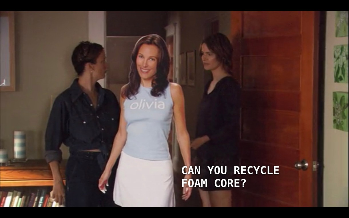 "Alice (wearing a short black dress) stands in the doorway of her apartment with a house cleaner (a woman wearing a long chambray shirt and her hair braided). The lifesize cutout of Dana is in between them. Alice asks, ""Can you recycle foam core?"""