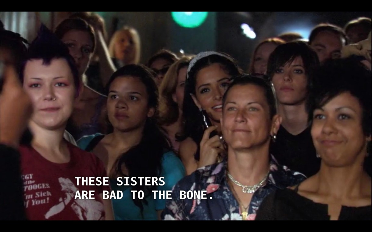 "Carmen stands in the crowd, surround by people, at a concert. Off screen, Kit says, ""these sisters are bad to the bone."""