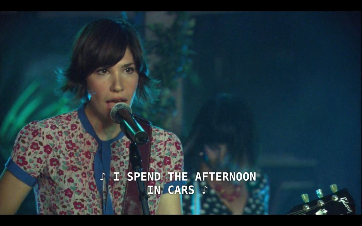 "Carrie Brownstein (playing herself in Sleater-Kinney) stands at the microphone on stage performing a concert. She is holding her guitar and has brown short hair that flips out at the ends, and she is wearing a short-sleeve floral shirt. She sings, ""I spend the afternoon in cars"""