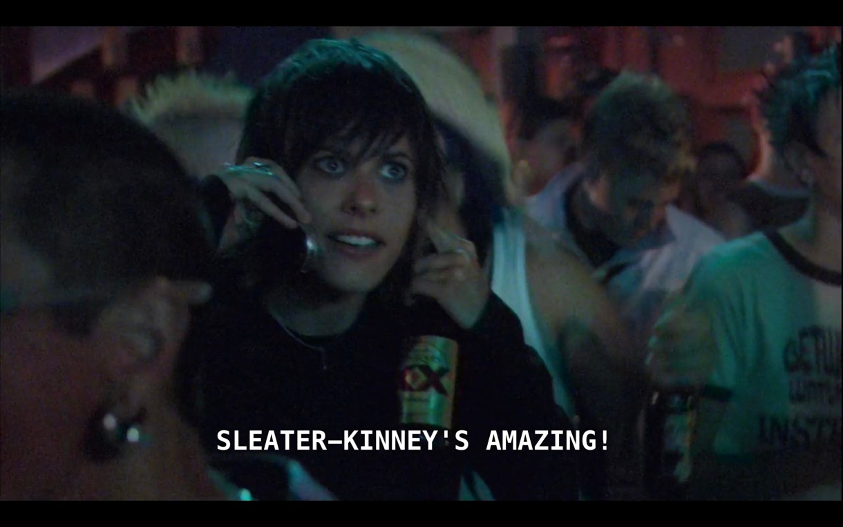 "Shane is standing in the crowd at the Sleater-Kinney concert. She is holding a bottle of Dos Equis beer and talking on her cell phone. She says, ""Sleater-Kinney's amazing!"""