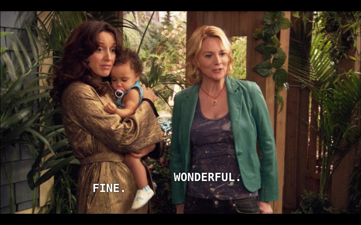 "Bette (wearing a brown jacket) is holding Angelica (wearing a blue shirt and a pink pacifier) next to Tina (wearing a blue blazer) in their driveway. Bette says ""Fine"" and Tina says ""Wonderful"" to the adoption social worker (off camera) who has just arrived."