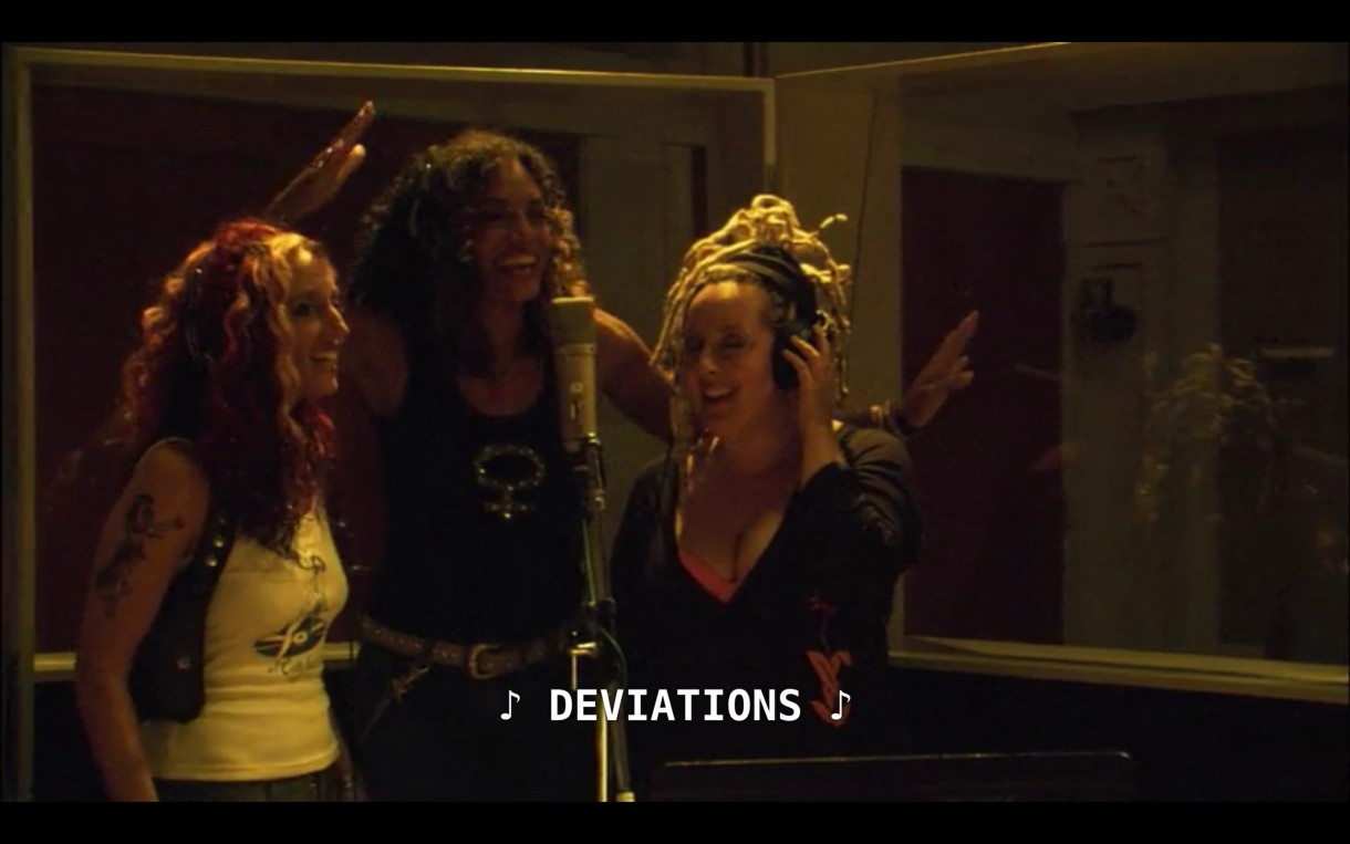 "The 3 band members of Betty are standing around a microphone in a recording studio. The subtitles show that they are singing the lyric ""Deviations."""