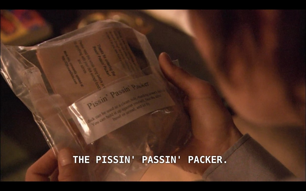 "Max is holding in his hands a plastic wrapper that reads ""Pissin' Passin' Packer"""