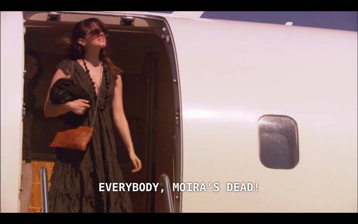 "Jenny (wearing a dark brown dress and sunglasses) steps off a private plane. She says, ""Everybody, Moira's dead!"""