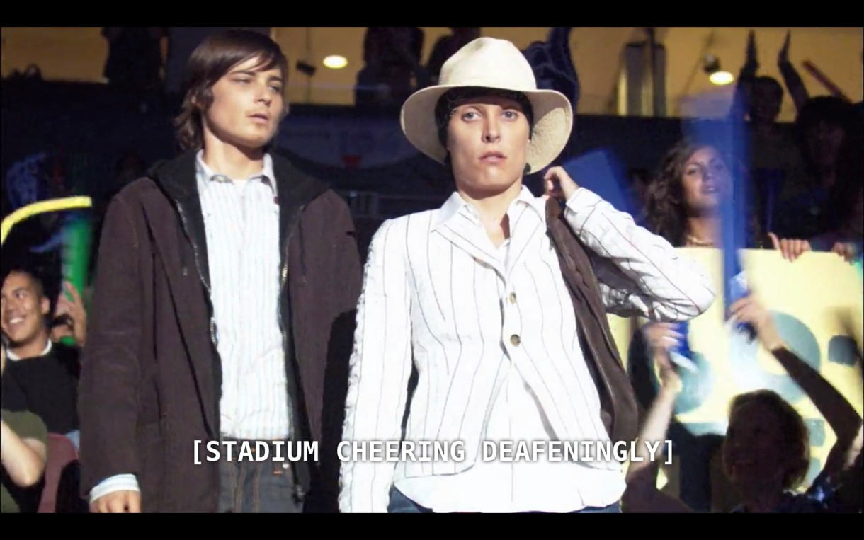 "Max and Dana (who is wearing a large white fedora, mind you) stand in a crowded stadium bleachers. The subtitles read ""[stadium cheering deafeningly]"""