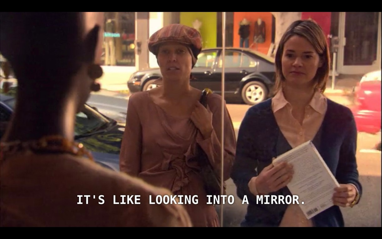 """Dana and Alice are looking in a storefront window at a bald mannequin (whose back is to the camera). Dana says, """"It's like looking into a mirror."""""""
