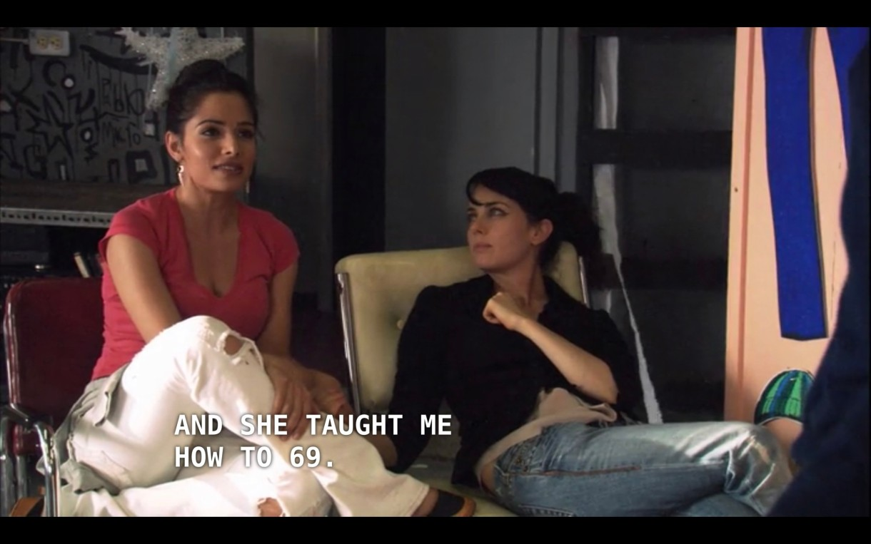 """Carmen (wearing white jeans and a pink top) sits next to Jenny (wearing blue jeans and a black top) in a modern-looking apartment. Carmen says, """"And she taught me how to 69"""" referring to her prom date, Eva Torres."""