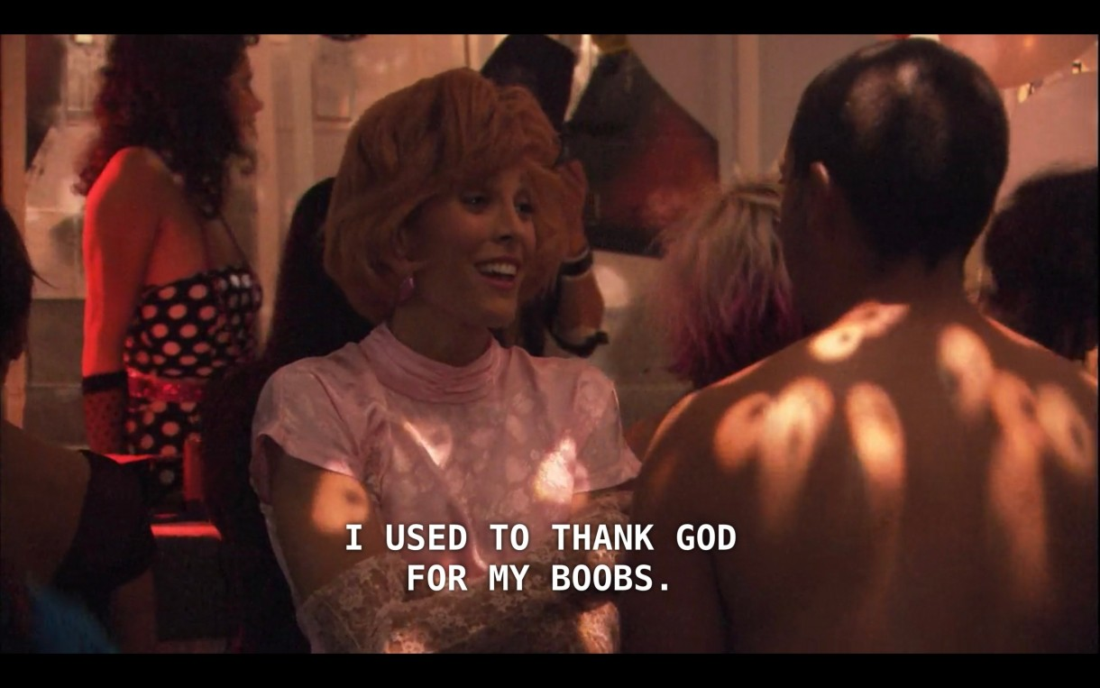 """Dana is at Queer Prom wearing a short blonde wig, a pink prom dress, and white lace gloves. She says, """"I used to thank God for my boobs."""""""