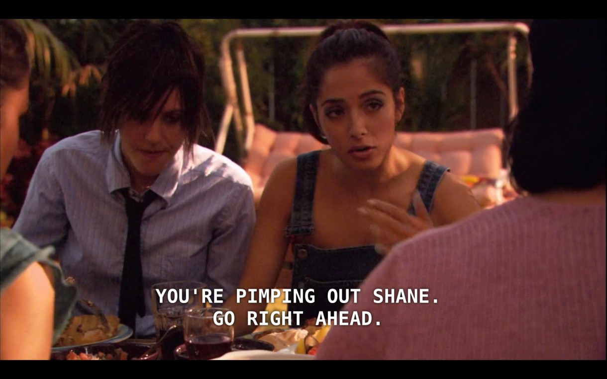 """Shane (wearing a blue button-up and a skinny black tie) sits next to Carmen (wearing jean overalls) at a picnic table where they're having dinner with Carmen's family. Carmen says to her mom, """"You're pimping out Shane. Go right ahead."""""""
